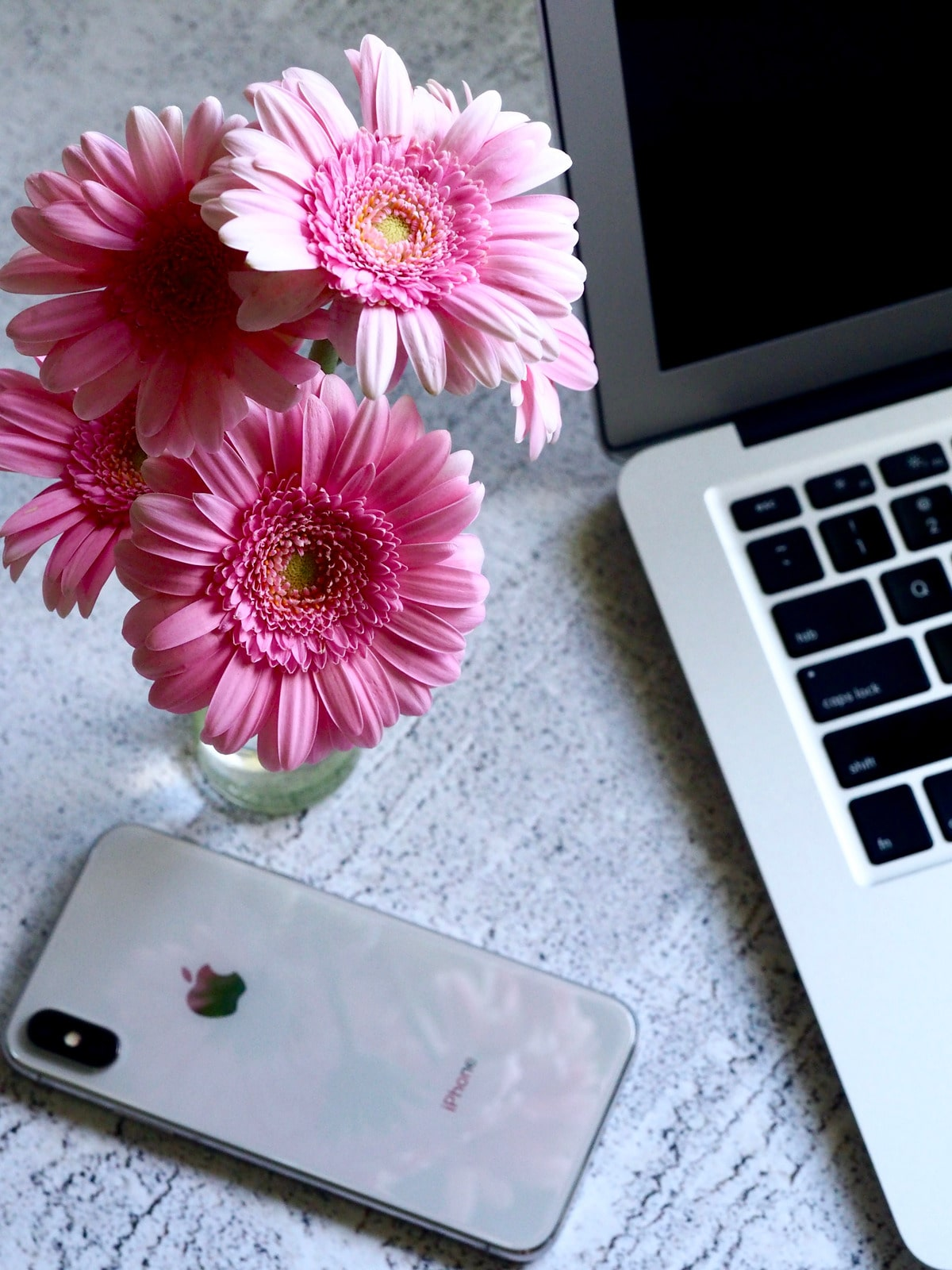 silver iphone x with pink daisys and macbook